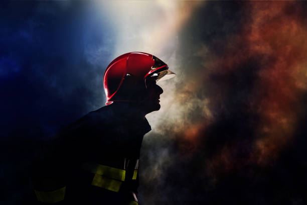 Firefighter silhouette in a smoke Silhouette of firefighter in a smoke. Fire and blue lights background. smoke jumper stock pictures, royalty-free photos & images