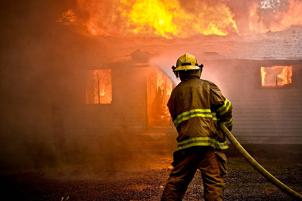 firefighter spraying water at a house fire - fire stok fotoğraflar ve resimler