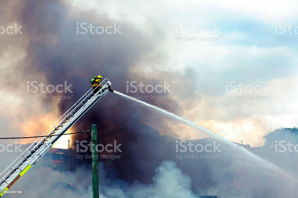 Firefighter spraying water on burning house, background with copy space stock photo