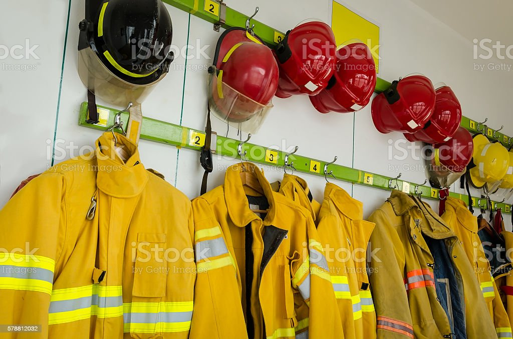 Firefighter suits and helmets hanging - foto de acervo