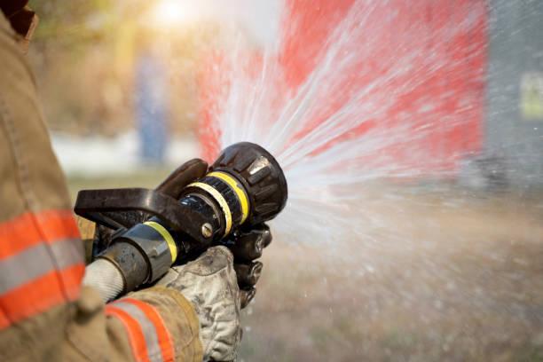 Firefighter using extinguisher stock photo