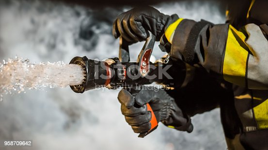 Close-up of firefighter using extinguisher after accident.