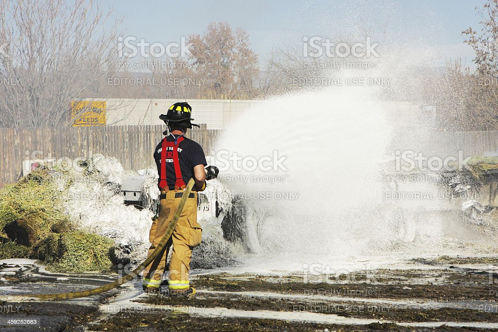 Firefighter Using Firehose Extinguishes Fire royalty-free stock photo