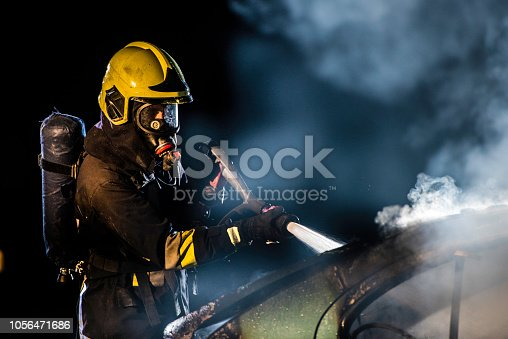 Portrait of a fireman at work using a fire hose to extinguish a vehicle fire at night.