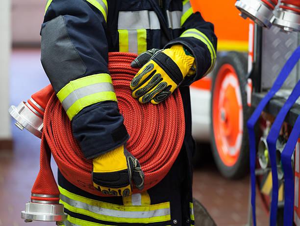 bombero usa un arrollado de manguera - bombero fotografías e imágenes de stock