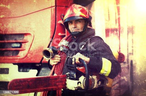 Firefighter with chainsaw and fire hose in the Wings. Grunge effects added.