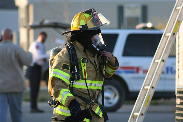 Firefighter Woman Female Firefighter preparing herself before she enters a burning building. smoke jumper stock pictures, royalty-free photos & images