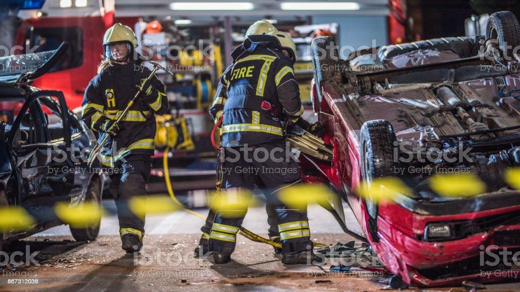 Feuerwehrmann arbeiten über Kopf Auto – Foto