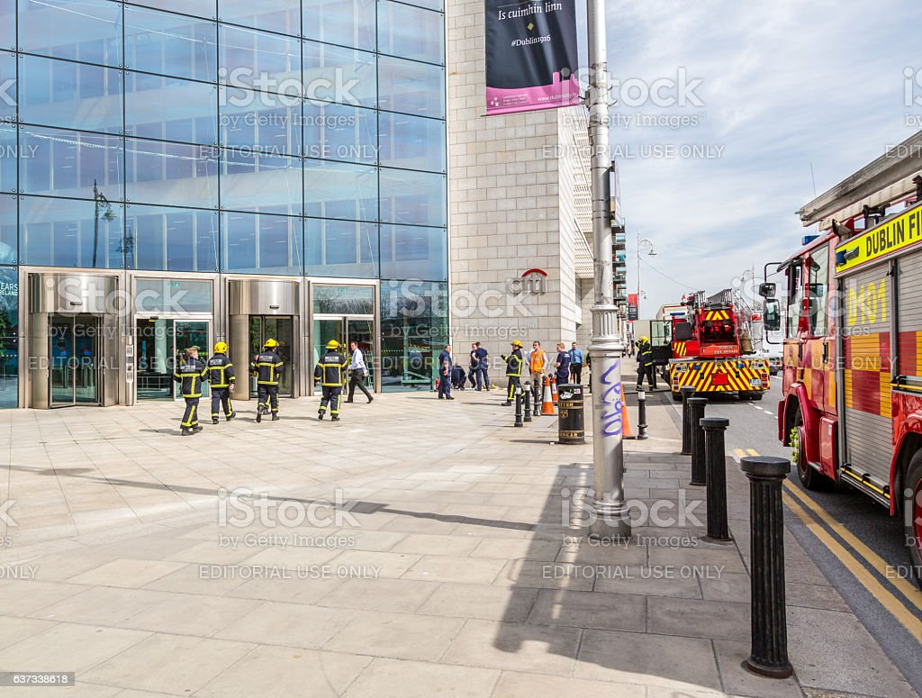 Firefighters and fire engines outside office building. stock photo