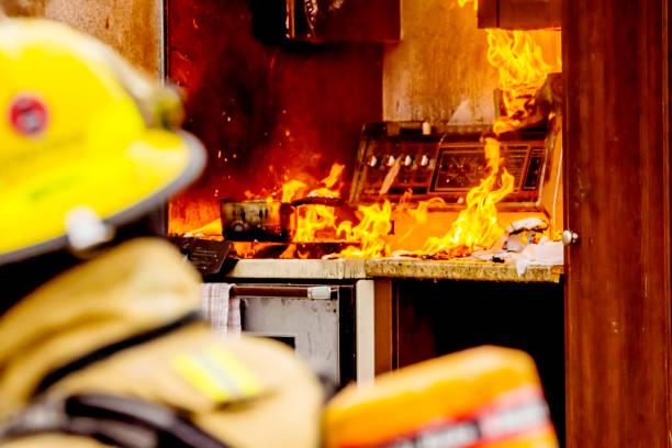 Firefighters and kitchen fire Des pompiers et un feu de cuisinière. Les pompiers en premier plan. fire natural phenomenon stock pictures, royalty-free photos & images