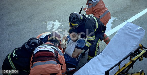istock Firefighters and paramedics lifting injured male cyclist onto stretcher 1045845504