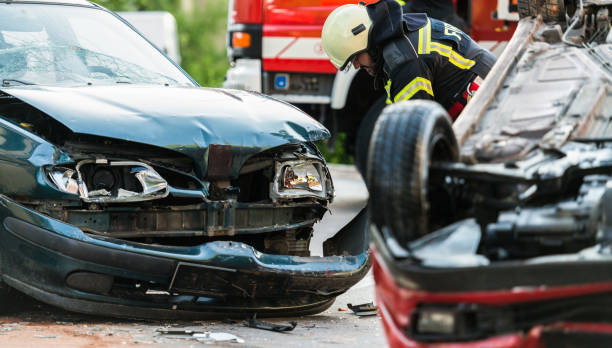 Firefighters At A Car Accident Scene Firefighters At A Car Accident Scene misfortune stock pictures, royalty-free photos & images