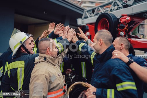 Group of firefighters putting hands together