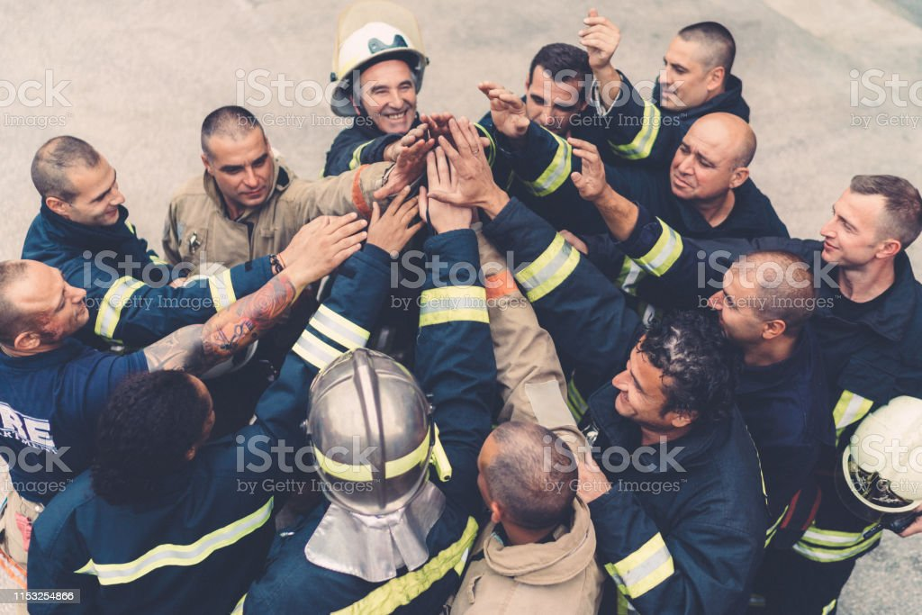 Firefighters doing high five Above view of firefighters putting hands together Achievement Stock Photo