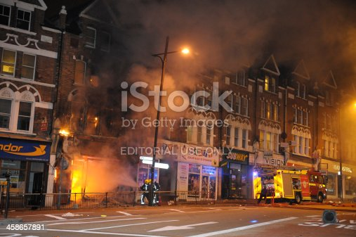 London, England, United Kingdom - August 8, 2011: Firefighters tackle fire at Party Superstore on Lavender Hill, Clapham Junction after it was set alight by arsonists during London riots.
