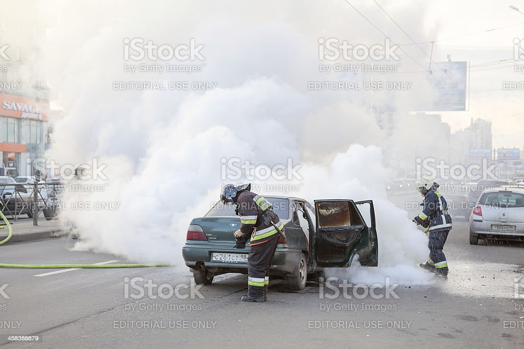 Firefighters extinguish burned car in city royalty-free stock photo