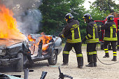 Val Della Torre, Italy - September, 28 2014: Demonstration switching off a car in flames by the Italian firefighters volunteers. Demonstration held in June 2015 in the province of Turin in Piedmont (Italy)