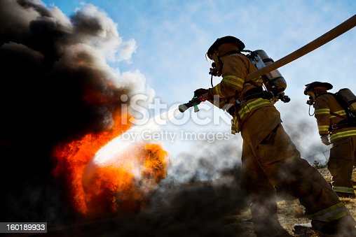 Firefighters in a fire protection suit wearing firefighter helmet with breathing device and holding fire hose is extinguishing a burning house fire that is putting off excessive heat and smoke.  Fire could have been caused by accident or arson.  Second firefighter in background.