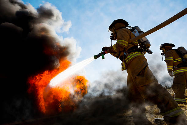 Firefighters Extinguishing House Fire stock photo
