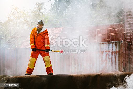 istock Firefighters fighting a fire operation, fireman holding ax, Firefighters extinguish burning warehouse 1142957861