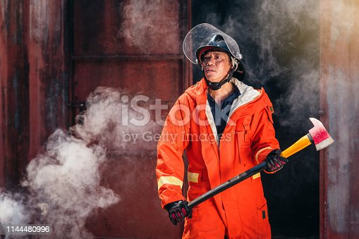 istock Firefighters fighting a fire operation, fireman holding ax, Firefighters extinguish burning warehouse 1144480996