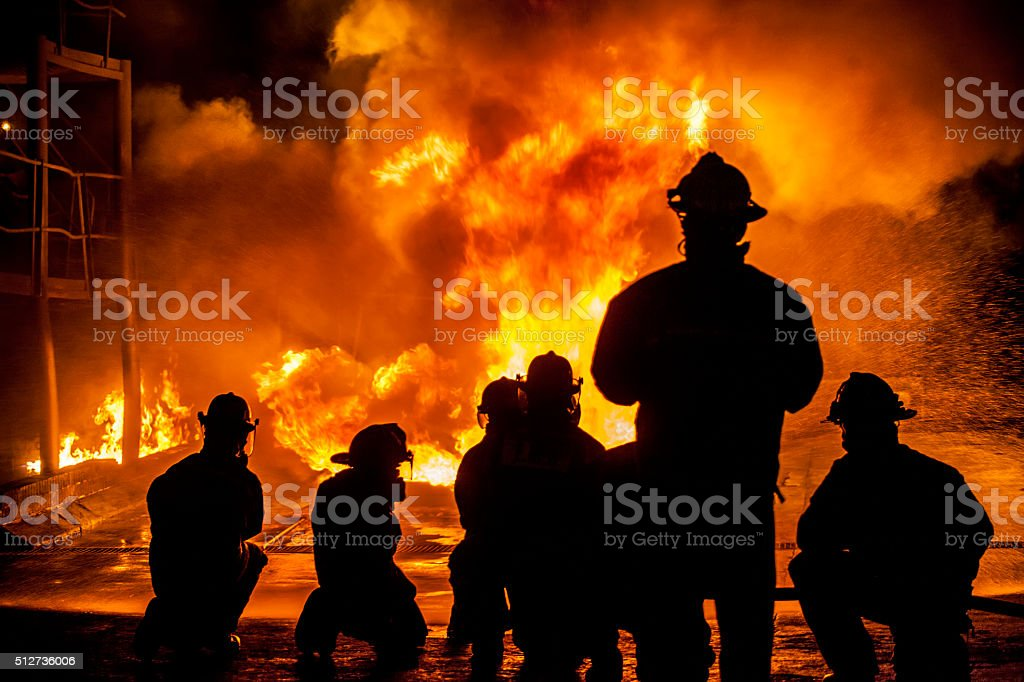 Firefighters fighting burning blaze stock photo