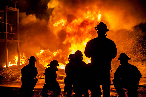 firefighters fighting burning blaze - firefighter stock photos and pictures