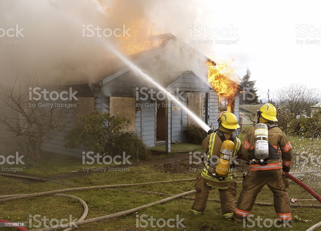 Firefighters Fighting Residential House Fire stock photo
