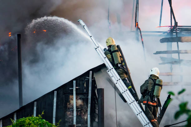 Firefighters fills the fire with water on roof of the hose standing on the stairs against a background of thick white smoke.. It's dangerous work. stock photo