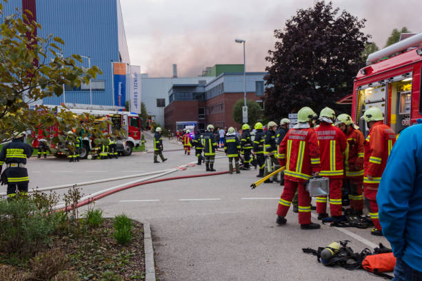 Firefighters fire truck portable crane at fire in paper factory