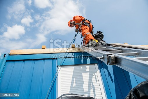 Firefighters in a rescue operation - accident on the roof; all logos removed. Slovenia, Europe. Nikon.
