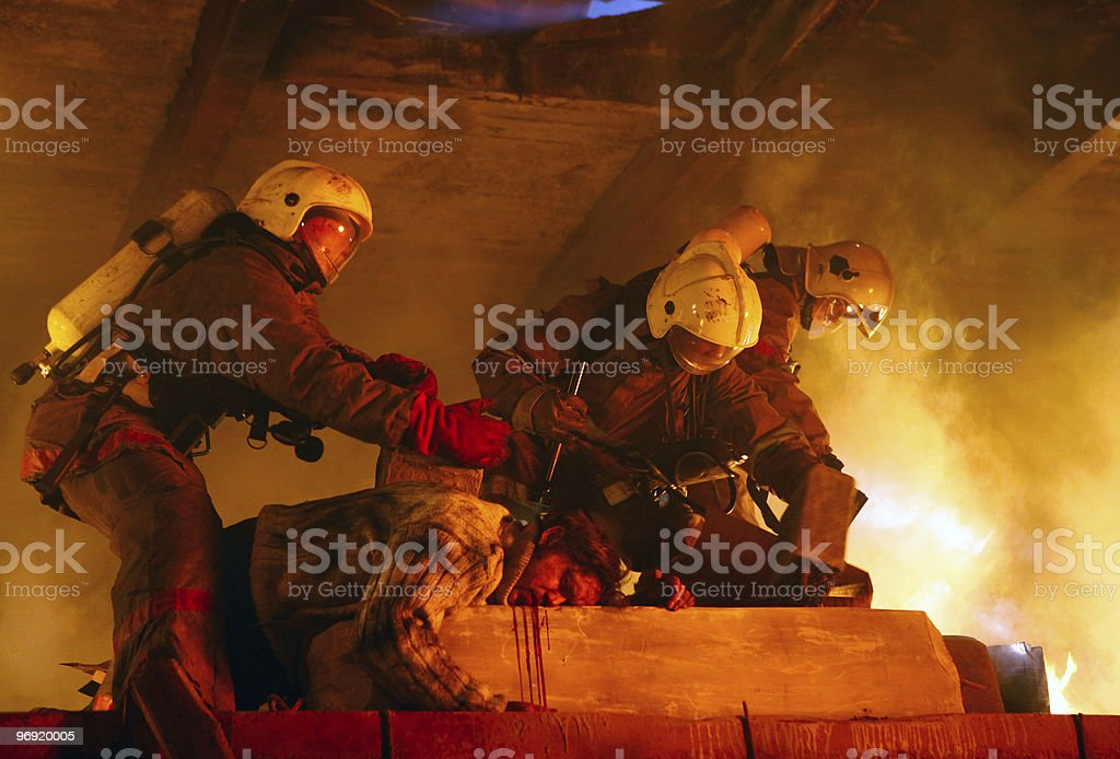 Firefighters in flames rescuing an accident victim royalty-free stock photo