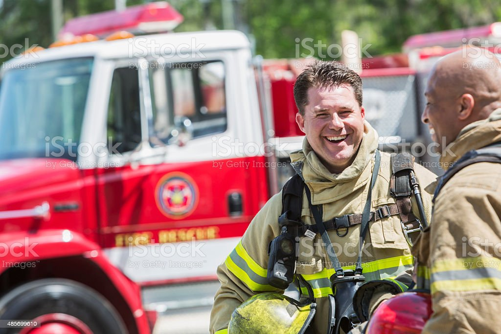 Firefighters in protective gear with fire rescue truck stock photo