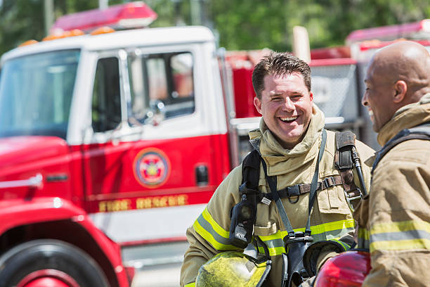 firefighters in protective gear with fire rescue truck - firefighter stock photos and pictures