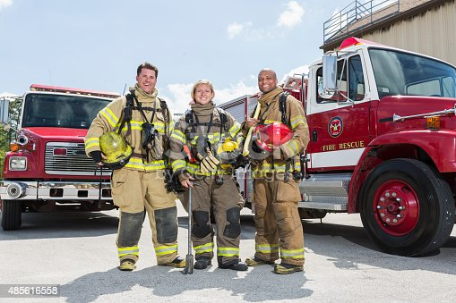 A team of three multiracial firefighters standing in protective suits and gear in front of two fire rescue trucks.  They are a diverse group, including a woman and an African American man, smiling at the camera.