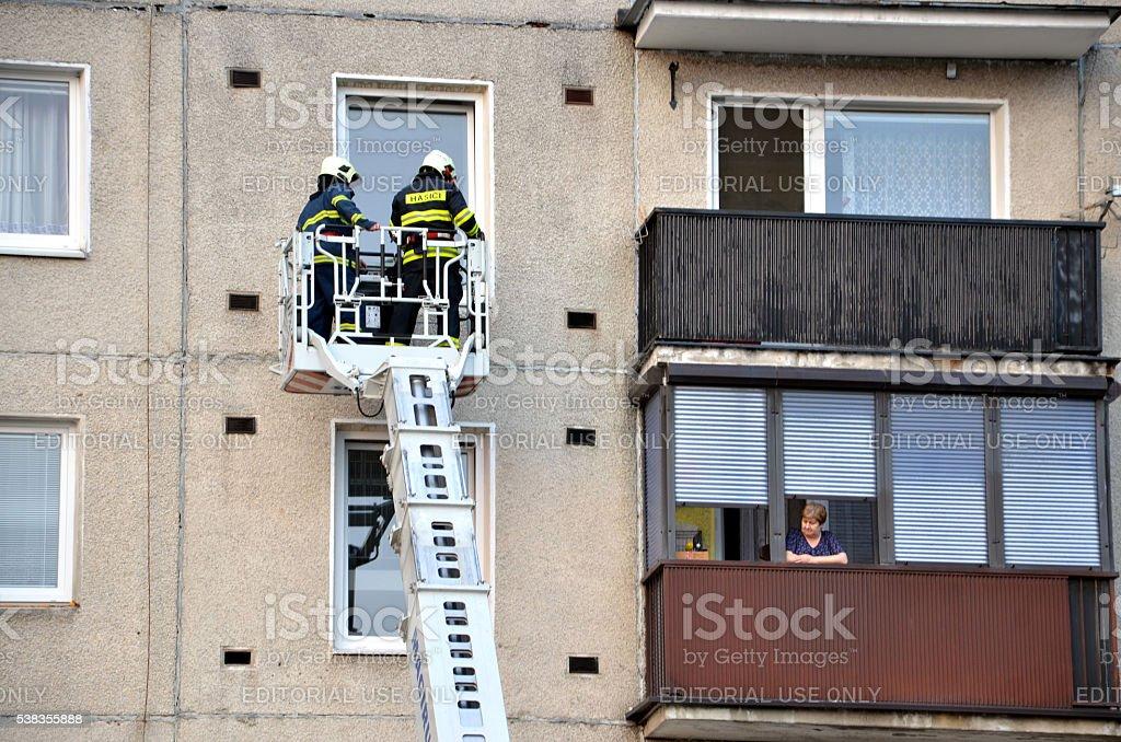 Los bomberos en micrófono pluma cesta intentar conseguir con balcón - foto de stock