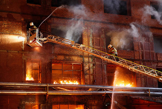 Firefighters on ladder fighting fire in brick building stock photo