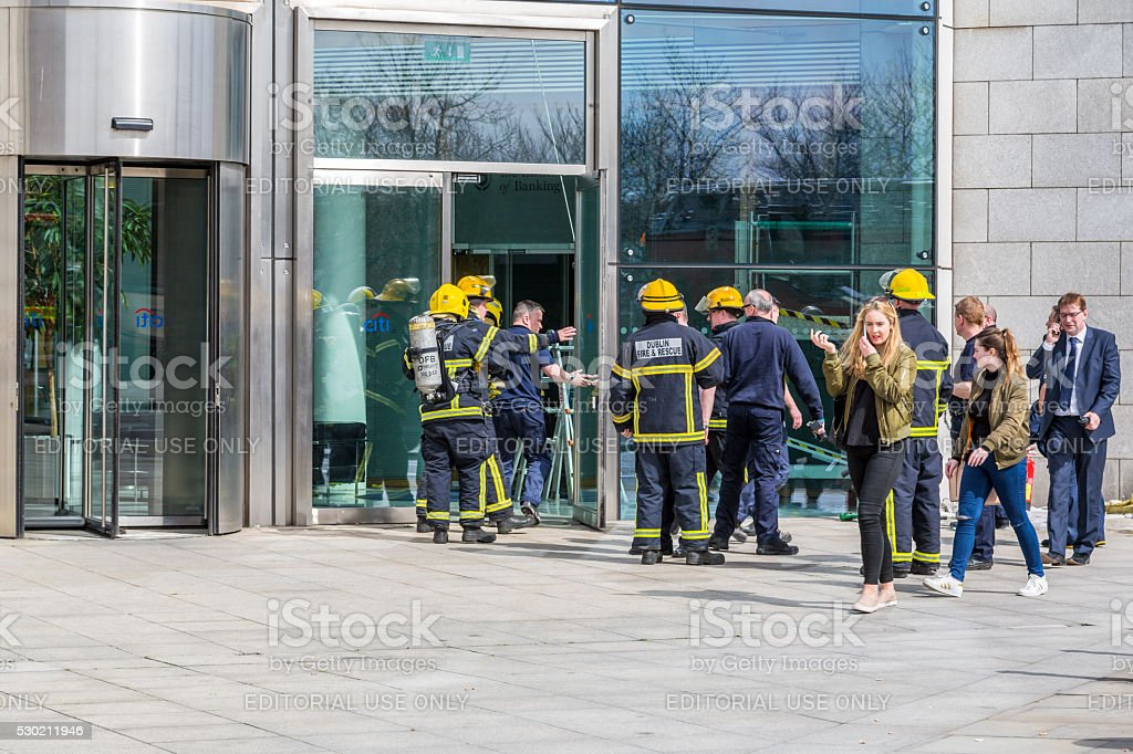 Firefighters outside office building. stock photo