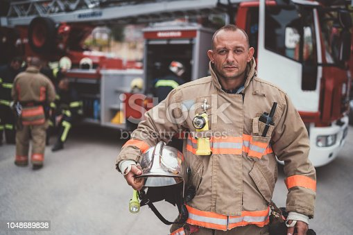 Firefighter with work helmet under arm looking at camera