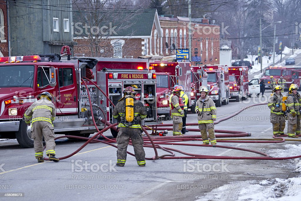 Firefighters preparing equipment during a house blaze. stock photo