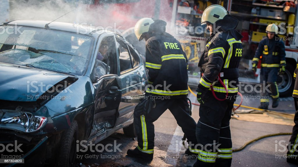 Firefighters rescuing driver stock photo