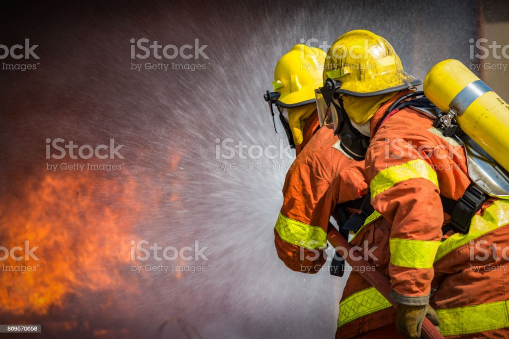 2 firefighters spraying high pressure water to  fire stock photo