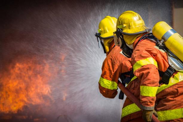 2 bomberos rociando agua a alta presión a fuego - bombero fotografías e imágenes de stock