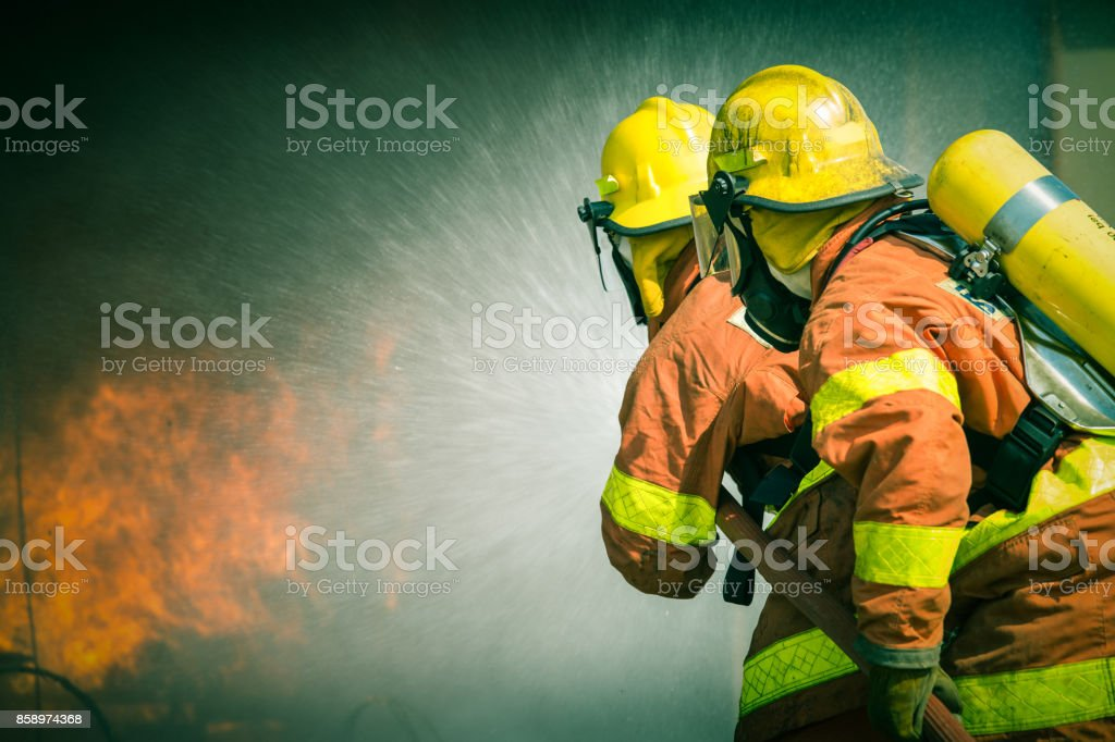 2 firefighters spraying water in cinematic tone stock photo