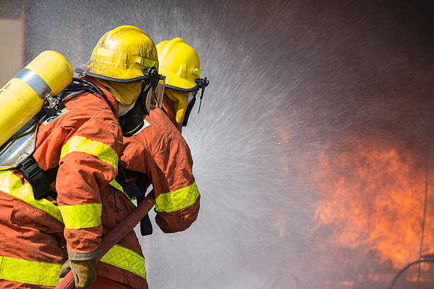 2 bomberos pulverización de agua en funcionamiento de extinción de incendios - bombero fotografías e imágenes de stock