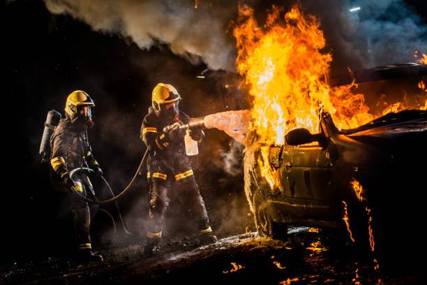 bomberos rociando agua sobre la quema de coches - bombero fotografías e imágenes de stock