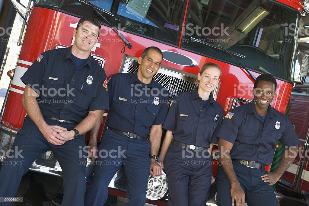 Firefighters standing by a fire engine stock photo