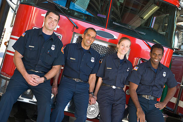 firefighters standing by a fire engine - firefighter stock photos and pictures