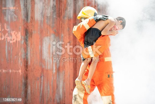 istock Firefighters training activity, Team practice to fight fire in emergency situation. A fireman run out with children from burning place. Fireman rescue young boy. 1283282149
