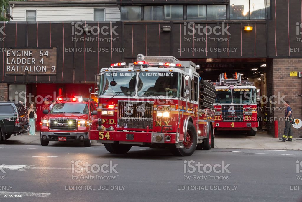 Firefighters trucks leaving their fire station stock photo